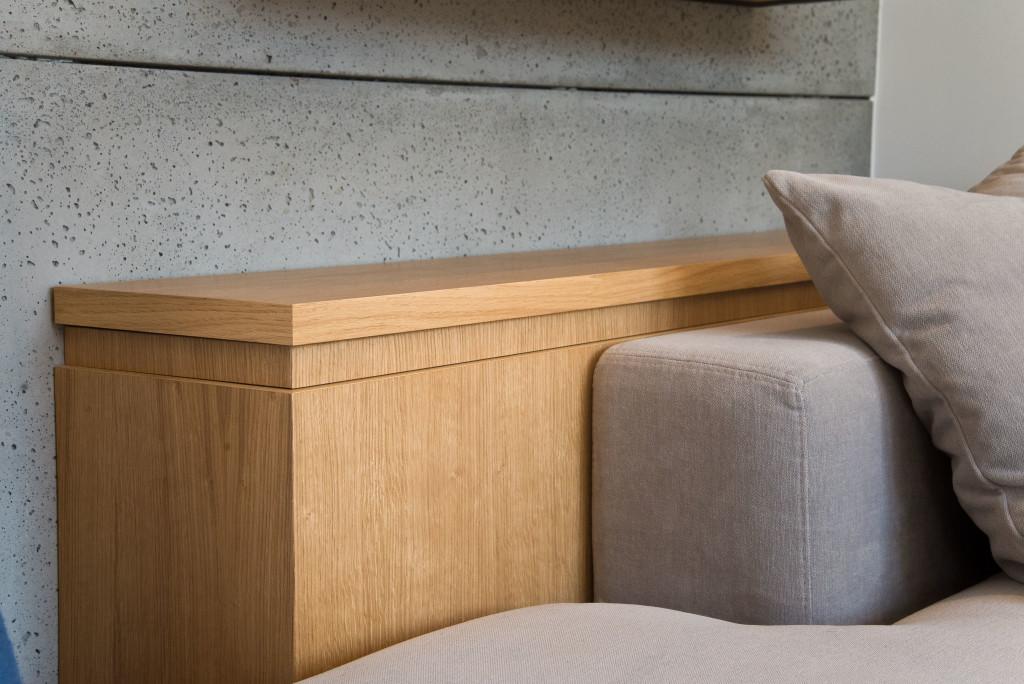 Imitacja betonu naścianie, drewniany regał, szara tapicerka - kwintesencja skandynawskiego stylu